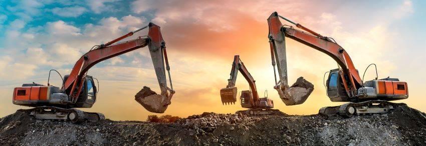 Saulėlydžio metu statybvietėje dirba trys ekskavatoriai
