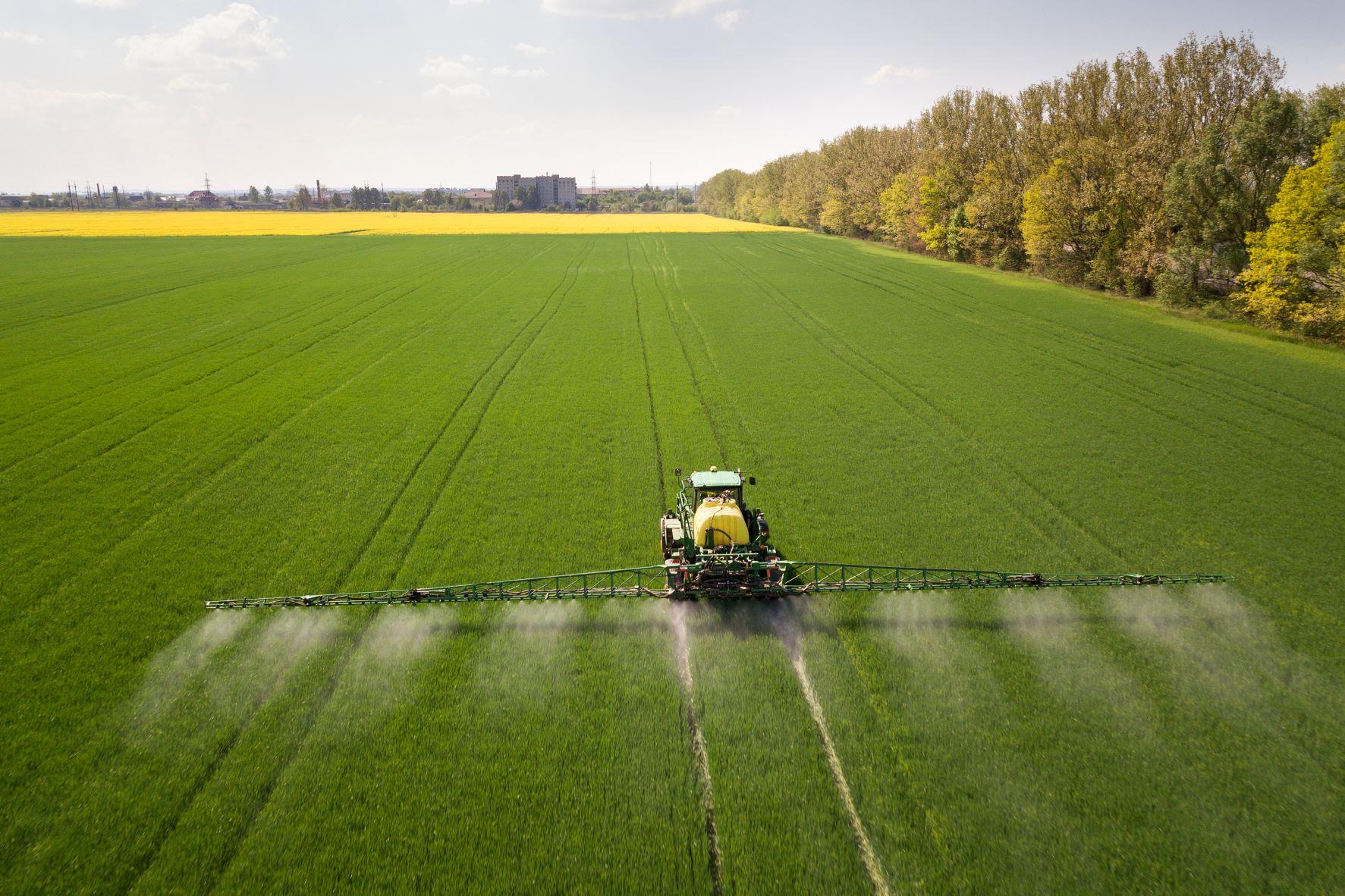 Traktorius pavasarį purškia cheminius pesticidus purkštuvu ant didelio žalio žemės ūkio lauko